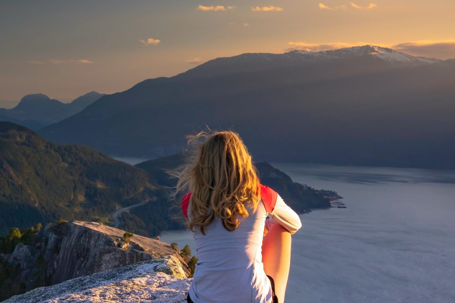 Woman sitting on mountain looking over river