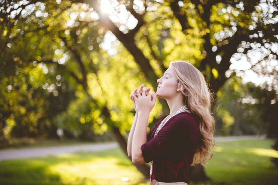 Woman in prayer outside by tree